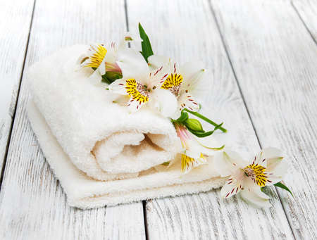 Spa towels and alstroemeria flowers on a wooden table Stock Photo