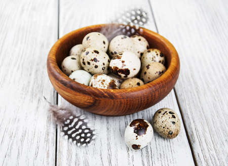 huevos de codorniz: bowl with fresh quail eggs on a old wooden table Foto de archivo