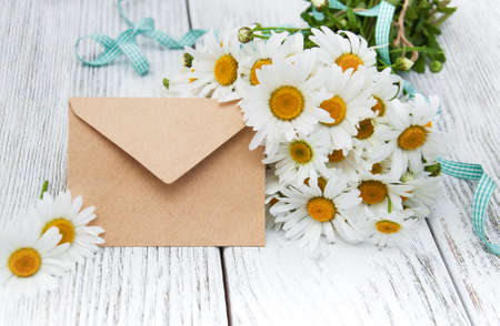 bouquet of daisies with envelope on a old wooden background