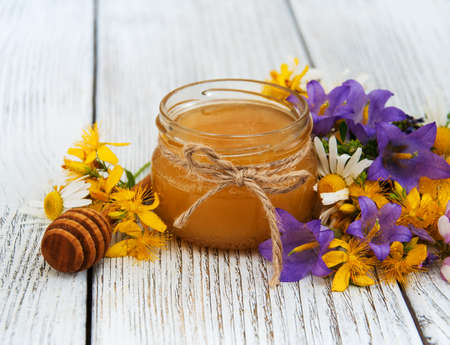 Jar of honey with wildflowers on a old wooden table Stock Photo