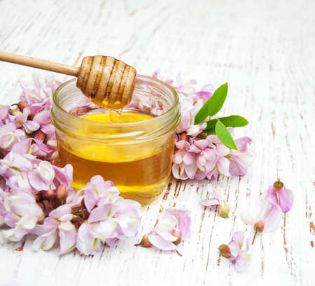 honey with acacia blossoms on a wooden background
