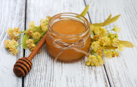Jar with honey and linden flowers on a wooden background Stock Photo