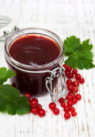 jelly beans: Redcurrants jam with fresh berries on a wooden background Stock Photo