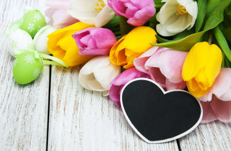 bunch of hearts: Easter eggs and tulips  on a old wooden table