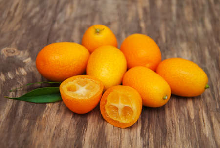 Fresh kumquats on a old wooden background
