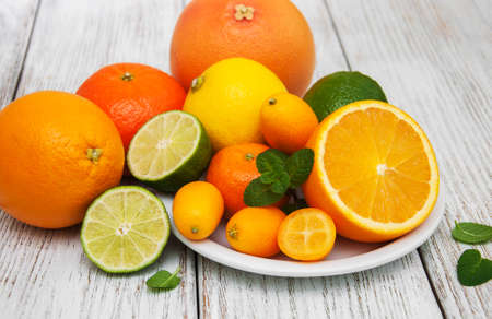Fresh citrus fruits on a old wooden table Imagens - 77620387