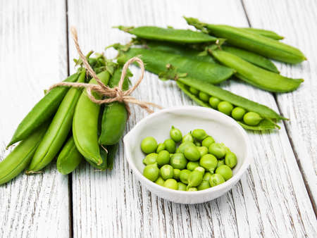 Green peas  on rustic white wooden background Stock Photo