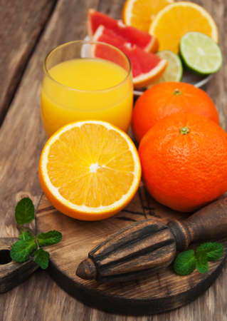 Glass of orange juice and fresh citrus fruits