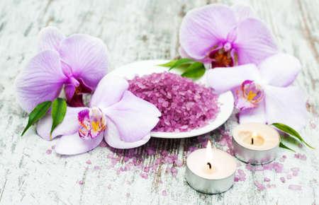 spa y productos de masaje con orquídeas en un fondo de madera vieja