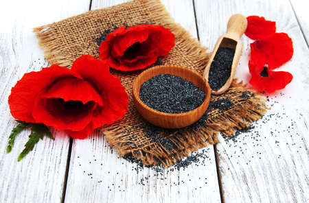 Poppy seeds and poppy flowers on a wooden background