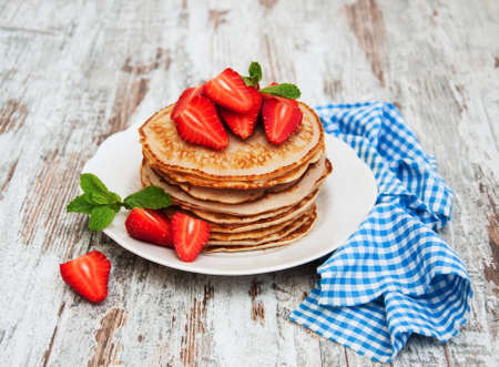 Pancakes with fresh strawberries on a old wooden background