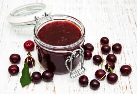 Cherry jam with fresh berries on a wooden background Stock Photo