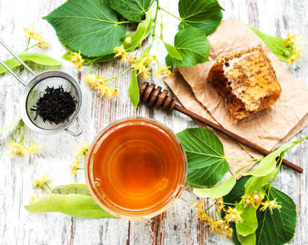 Honey comb, tea  and linden flowers on a board Stock Photo