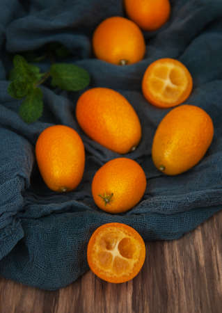 Fresh kumquats on a blue textile napkins