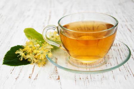 tilo: cup of herbal tea with linden flowers on a old wooden background
