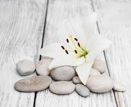 White lily and massage stones on a wooden table