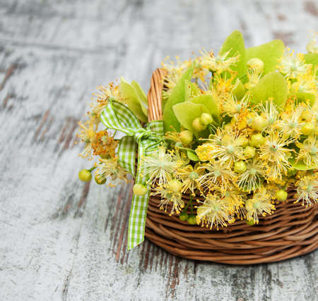 Basket  with linden flowers on a old wooden table