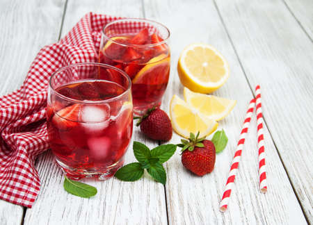 Glasses of lemonade with strawberries, lemon and mint on a old wooden table Stock Photo