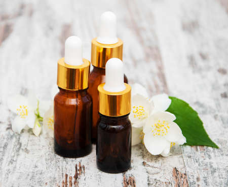 Massage oils and jasmine flowers on a wooden table Stock Photo
