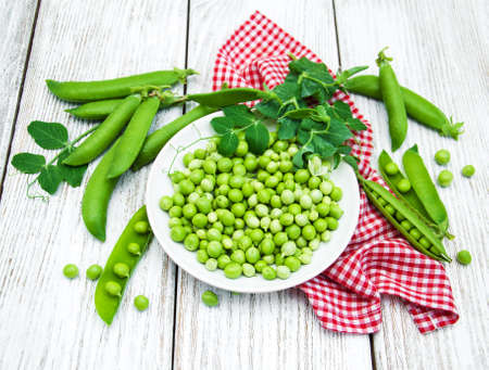 green peas  on rustic white wooden table