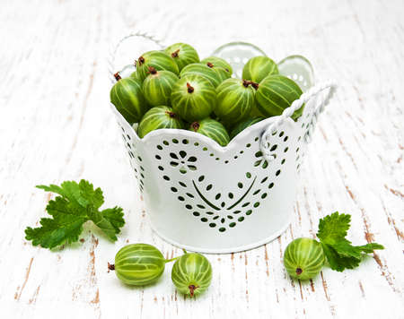 gooseberries with leaves on a old wooden table Stock Photo