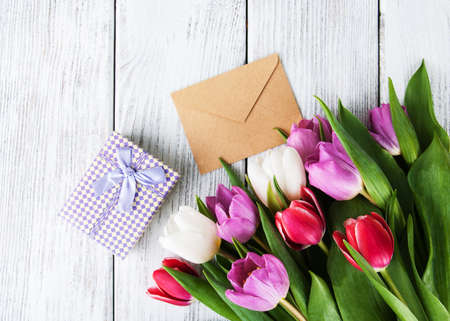 tulips bouquet and gift box on a old wooden table Stock Photo
