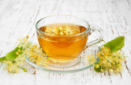 cup of herbal tea with linden flowers on a old wooden background