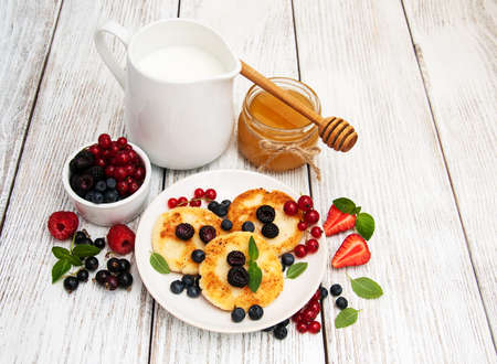 cottage cheese pancake with berries on a wooden table Stock Photo