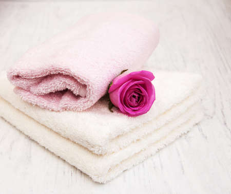 bath: Bath towels with pink roses on a old wooden background Stock Photo