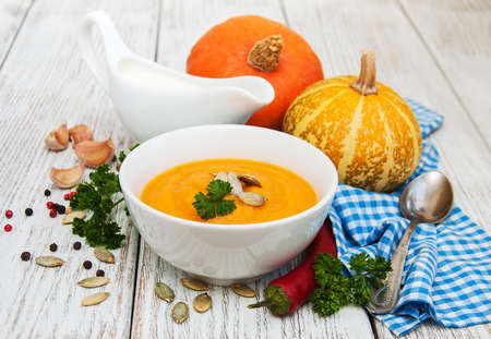 Pumpkin soup with fresh pumpkins on a old wooden table