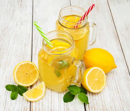 Potten met limonade op een oude houten tafel