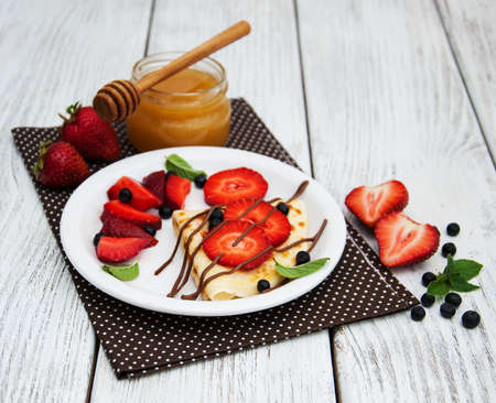 pancakes  with strawberries, blueberries  and chocolate sauce