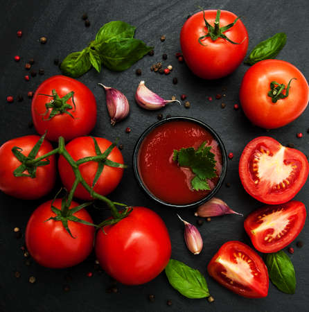 Bowl with tomato sauce and fresh tomatoes on a black stone background