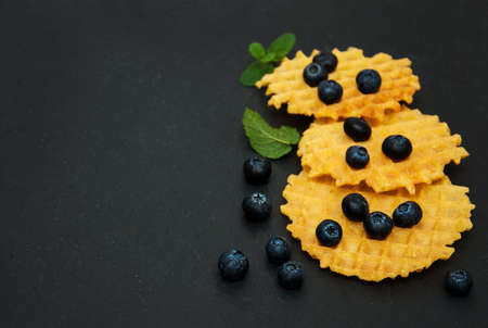 Waffles with blueberries on a black stone background