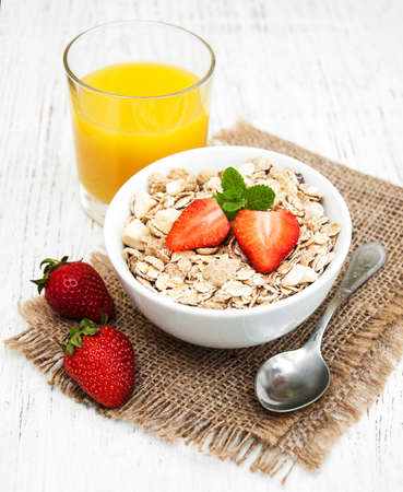 Muesli with strawberries on a old wooden background Stock Photo