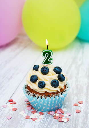 Cupcake with a numeral two candle on a table