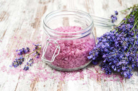Massage salt with lavender flowers on a table
