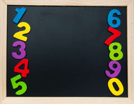 colorful wooden numbers on a blackboard background