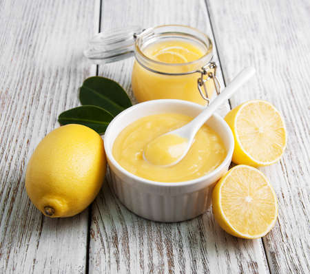 Lemon curd and fresh lemons on a old wooden table