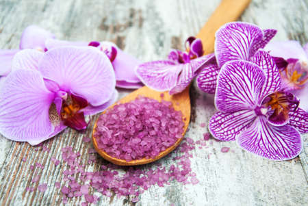 Spa salt and orchids on a old wooden background