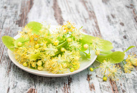 Plate  with linden flowers on a old wooden table