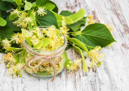 linden flowers in a jar on a old wooden table