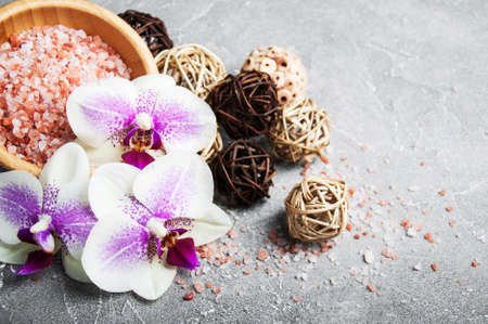 Spa products with orchids on a old gray stone background
