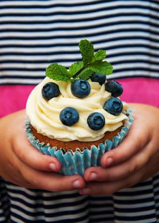 Little girl holding birthday cupcake with blueberries 스톡 콘텐츠