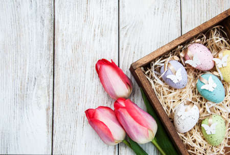 Easter eggs and tulips on a wooden table