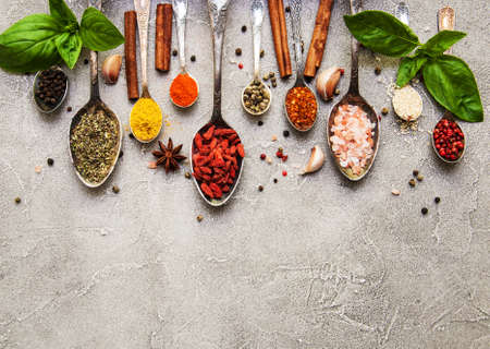 Different kind of spices in vintage spoons on a gray stone background