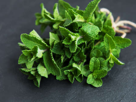 Fresh green mint on a black stone background Stock Photo
