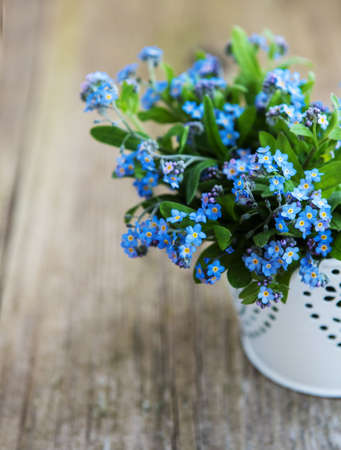 Forget-me-not flowers in small metal bucket on old table