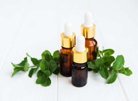 essential aroma oil with mint on a white wooden table Stock Photo