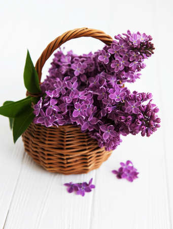 basket with a branch of lilac flower